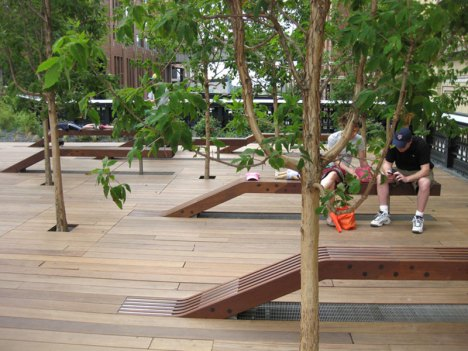 Wooden peel-up benches in the trees at the Tenth Avenue Square